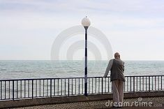 A single senior man by himself looking out to sea on Eastbourne promenade in Sussex England. Eastbourne has a high population of senior people.