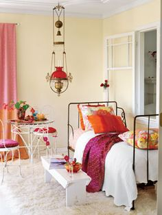 Touches of deep aqua blue balance out the saturated reds, pinks, and oranges in this colorful bedroom.