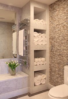 Inspiration from Bathrooms.com: A clever way to keep towels neat, on hand, and to create a display of touchable texture - open shelves. Use them to display bathroom bottles, too. #bath #bathroom #spa #wetroom