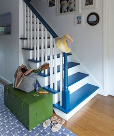 A Garnet Hill rug and porthole-shaped mirror reinforce the nautical vibe of this family-friendly New York home's staircase, painted in Benjamin Moore's Big Country Blue. The trunk was a flea-market bargain. Painted Stair Risers, Painted Staircases, Stairs Balusters, Bannister, Farmhouse Stairs, Escalier Design, White Stairs, New York Homes, Stairway To Heaven