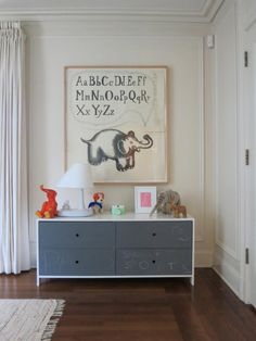 A chalkboard painted dresser from Duc Duc and a framed ink drawing by Jeffry Mitchell. The lamp is from Lladro's ReDeco series. Pinch pleat drapes and molding on walls.