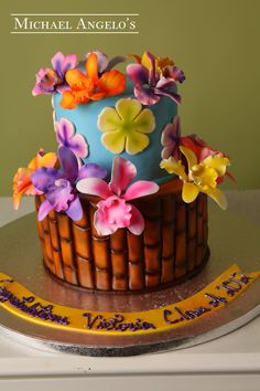Aloha Graduation #46Graduation This design is not your typical graduation cake but the Hawaiin theme will sure have your guests in awe! It is full of brightly colored tropical flowers that are cut out from fondant and matching gum paste flowers to add some depth. The bottom layer is textured just like a tropical tree.