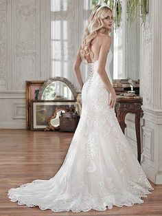 Lovely in lace, this fit and flare wedding dress is the epitome of beauty with bold lace appliqués laying atop tulle, cascading to a subtly flared skirt. Finished with sweetheart neckline and corset c