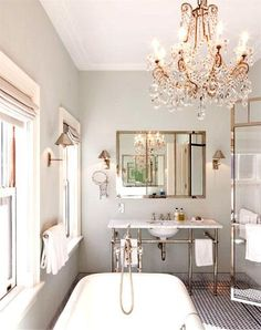 Katie Lee's Home- Gray & gold master bathroom design with gray walls, marble washstand, silver mirror, polished nickel sconces, gray silk roman shades, claw foot tub, glass shower, marble basketweave tiles and crystal chandelier.