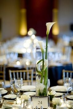 White calla Lily were very popular 20s flower. Seems like vertical look, single flower or simple, strappy grass or such like.