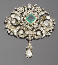 A possibly 18th century diamond and emerald brooch/pendant  The central square cut-cornered emerald, within a scalloped rose-cut diamond border, with an outer surround of scrolling tendrils and floral and leaf sprays, the whole suspending a rose-cut diamond drop, mounted in silver and gold