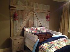 Barn door headboard for a toddler bed with wired Edison bulb lights. #barndoor #headboard #lantern #edisonbulb
