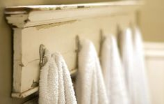 A piece of molding with hooks attached is a cheap and rustic towel rack.