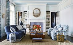 Crisp white walls with woodwork picked out in a soft blue created architectural interest and definition in a room with high ceilings. Designed by Andrew Howard