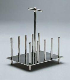 Movimiento Arts Dresser. Considerado como el primer diseñador industrial, realiza diseños para las manufacturas británicas. Es un innovador y funcionalista, anticipándose a los diseños de la Bauhaus. Lineas limpias, geometría pura...y estamos hablando de finales del S XIX. Soporte para tostadas