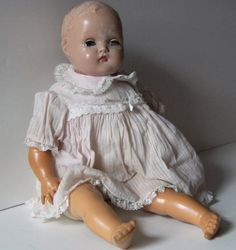 Antique doll - I had one that looked very similar to this one. I named her Mary Jane (after the candy). I left her outside one night and the moisture in the overnight air cracked her. She had two teeth and a small tongue (made of red felt). I tried feeding her a baby bottle and pushed her teeth and tongue back into her mouth. :( I was never able to pull them out.