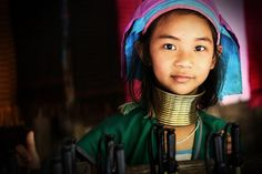 AMAZING THAILAND:  A young girl from the Karen tribe at Chiang Rai Province, Northern Thailand while showing her appearance to the public with her unique brass rings at the neck. ♥  These Karen people live along the borderline between Thailand and Myanmar and often speak their own languages and have their traditional tribe cultures.
