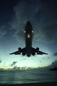 MD11 landing at St. Maarten Princess Juliana at sunset. View from Maho Beach.