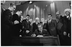 President Lyndon Johnson signs the 1968 Civil Rights Act into law as a group of legislators, including Senator Walter Mondale, looks on.