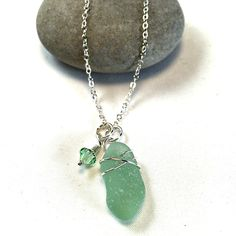 A pretty custom pendant featuring a piece of sea foam green sea glass with a crystal accent.
