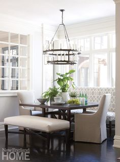 Dark and light make fine companions in the breakfast area, where seating outfitted in a mix of pale fabrics comes together around a custom table illuminated by a two-tier ring chandelier.