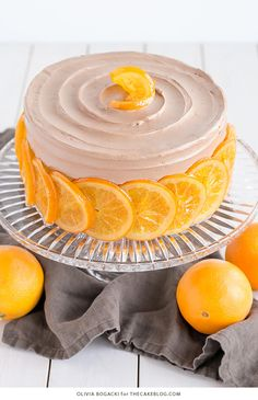 Chocolate Orange Cake - layer cake infused with orange zest and orange syrup, topped with chocolate frosting and candied orange slices   By Olivia Bogacki for TheCakeBlog.com
