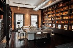 Dark Etageres / open bookcases and matching floor against exposed reddish brick. Décor de Provence