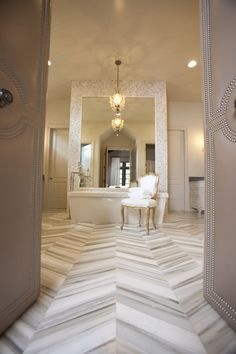Upholstered door with nail head trim, marble herringbone tile, mosaic tiled over-sized mirror... So many things to love about this bathroom! Blissful Bathtubs We Love at Design Connection, Inc. | Kansas City Interior Design http://www.DesignConnectionInc.com