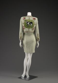 Suit   Franco Moschino (Italian, 1950-1994)   Italy, 1991   Materials: wool, acrylic, silk, metal   Moschino, known for his irreverence regarding the fashion system, pokes fun at one of couture's most famous designers, Gabrielle 'Coco' Chanel. Using immaculate construction, he imitates the classic Chanel suit but juxtaposes discordant imagery to create a humorous work   Indianapolis Museum of Art