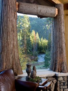 A luxurious log cabin room with a view of the forest! Looks like maybe live trees, stone slab table, rock base, maybe even glass?