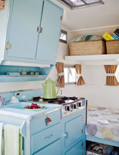 Glamping Kitchen in trailer is very cute with the baby blue cabinets.