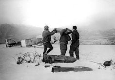 """Axis Italian airmen of the Royal Italian Air Force (Italian: Regia Aeronautica) prepare aerial bombs in Italian-occupied northern Albania for a sortie over Allied Greek positions during the Greco-Italian War. In the background can be seen a Savoia-Marchetti SM.79 """"Sparviero"""" three-engine medium bomber aircraft. The Greco-Italian War began on 28 October 1940"""