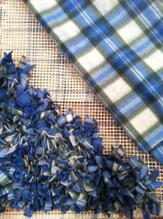 """Fleece Rug Fleece remnants cut into strips 3/4"""" by 4"""" long. Fleece stretches more in one direction than the other, so cut the strips in the direction that maximizes stretchiness Rug canvas  Cut off one of the ends at an angle Tie a tight knot Repeat, skipping a hole"""