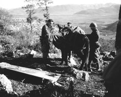 In the mountains near Venafro, an Italian mule skinner (right) helps secure the body of a dead American soldier for removal to a temporary military cemetery. Blood stains can be seen on the stretcher.