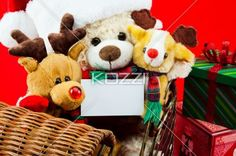 holiday toys - Holiday toys in a wicker sleigh holding a white card for copy space, with a red background.