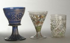 Standing-cup; blue glass; flat bottom with serrated and pearled rim, supported by fluted bell stem and foot covered with powdered gold; bowl decorated with central band of gilt leaflets and white enamel flowers, flanked by borders of gilt chain/twisted pattern between rows of white dots.