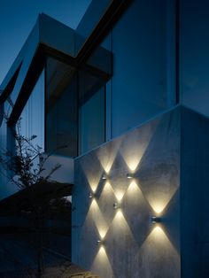 Juego de luces con apliques en el muro del jardín