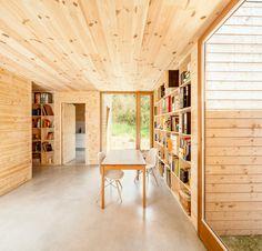 大きな作り付け本棚のある森の中のパッシブハウス