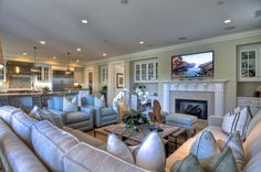 Coastal decor is found in the details in this spacious family room. upholstered light-sea blue chairs sit aside an off-white sectional sofa and additional Living Room Kitchen, Living Room Decor, Large Family Rooms, Family Room Design With Tv, Traditional Family Rooms, Big Family, Coastal Living Rooms, Spacious Living Room, Furniture Layout