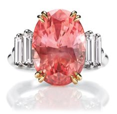 Sunset by Harry Winston, Padparadscha Sapphire and Diamond Ring. Oval padparadscha sapphire, 11.41 carats; 4 baguette diamonds, 1.24 total carats; 18k yellow gold and platinum setting.