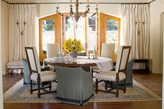 Just because the dining room is traditionally a formal space doesn't mean you can't try a more casual feel. Mixing high-back upholstered seating with low, slipcovered chairs avoids the predictable formula of a table with matching chairs in this room.  Tour this Texas Lake House