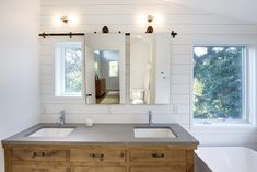 Barndoor Mirror : A solution to hang a mirror in front of a window.  We used an old metal door track and hung custom mirrors that slide to reveal the window and let in natural light or close for privacy and functionality.  Strand Design, Minneapolis, MN.