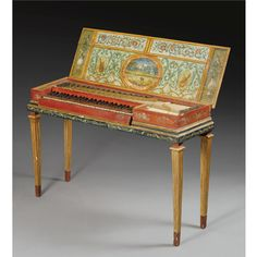 A fretted clavichord  Portugal or Spain ,  second half of the 18th century  the interior and exterior with extensive, probably later, painted decoration, the lid with a central panel painted with ruins and a village in an extensive landscape within a floral frame, with simulated wood grain crossbanding, the lid interior painted with an oval panel depicting a castle within a landscape, flanked by two simple musical trophies, the four and a half octave keyboard, C to f3,with possibly yew…