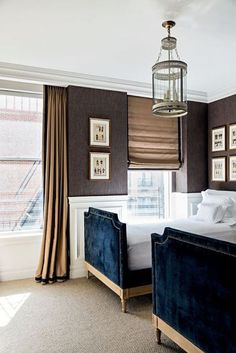 Chic, elegant boy's bedroom features a round lantern illuminating upper walls clad in brown textured wallpaper and lower walls clad in wainscoting lined with a pair of matching royal blue velvet French beds with silver nailhead trim dressed in white bedding. | Jorge Elias Retirement Home in New York Featured in Casa Vogue
