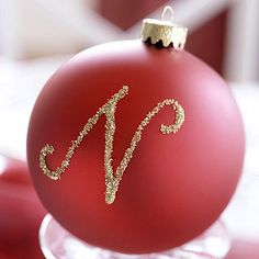 Dip a paintbrush into crafts glue to create the desired letter, then sprinkle with glitter. Let dry.