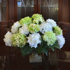 """Green and White Hydrangea Silk Flower Arrangement AR332. This extraordinary arrangement of silk hydrangeas in white and soft green will make a beautiful centerpiece for your home. Created with high qualith silk flowers, custom designed to fit your space in a pedestal resin vase. 24""""L x 18""""H"""