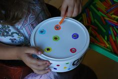 A Fine Motor Activity for Preschoolers to drop colored straws into the color coordinated whole. Teaches them colors and fine motor skills.