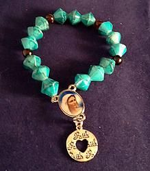 Mother Mary Turquoise Beaded Blessing Bracelet  Beautiful handmade stretch religious blessing bracelet with a Mother Mary focal charm. Stretch bracelet is made with Turquoise cone shape beads with coffee brown Quartz round beads in-between. The additional drop charm is written with he word, Faith on the disc shaped charm.