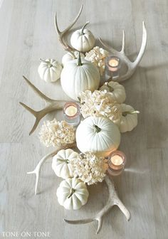 Fall table centerpiece of white pumpkins, antlers and hydrangeas