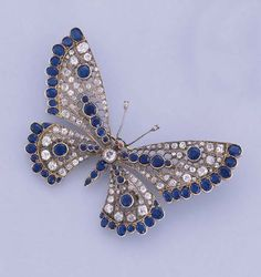 A SAPPHIRE AND DIAMOND BUTTERFLY BROOCH   The butterfly with sapphire and diamond wings set en tremblant to the similarly designed body and ruby collet eyes, millegrain setting, first half twentieth century, 8.9 cm. wide. [Best guess it's Edwardian/Belle Epoque]