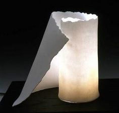 "These modern ceramic light sculptures are one-of-a-kind. Well-suited to modern décor, they are made of translucent porcelain, reminiscent of scrolls of parchment or sheer drapery. They sit on simple platforms of black-stained oak and range from 9"" to 20"" in height. For an even bigger impact, they may be used with color light bulbs."