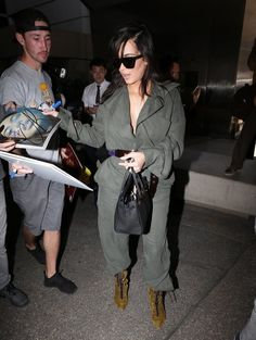 Kim Kardashian Photos Photos - Couple Kanye West and Kim Kardashian are seen arriving on a flight at LAX airport in Los Angeles, California on May 24, 2016. Kim and Kanye are returning from London where they attended The Vogue 100th Anniversary Gala Dinner. - Kanye West