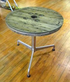 Wooden spool table. Eames aluminum base with a reclaimed wire spool top and glass to finish it off.