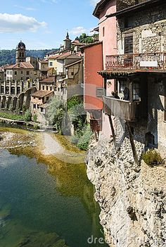A traditional old village in the Alpine region of Europe, with small hanging houses build with stone on a cliff over a river. Two church towers are rising over the playful skyline of the town. This ingenious architecture is spectacular. Regions Of Europe, Cliff, Towers, Building A House, Travel Destinations, Skyline, Houses, River, Stock Photos