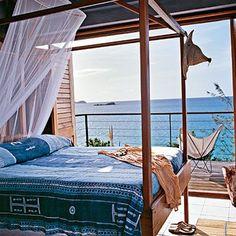 Bedroom open to water front | lounge chair on balcony | indoor outdoor living